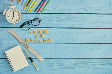 Back to School Concept with Stationery Supplies on blue wood work desk with flat lay copy space for text