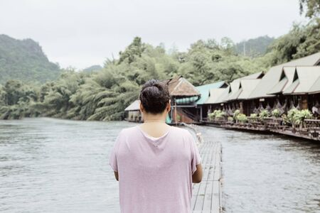 Back view of Asian young woman traveler travel and relax at the lake or river through the green forest