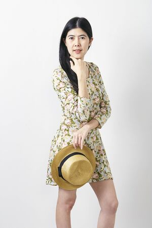 Attractive nice cute portrait  Asian young woman in floral spring summer dress with hat. Girl posing on a white background. Travel fashion concept