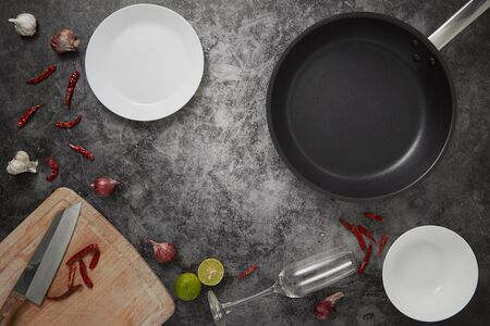 Top view empty frying pan and empty dishs by vegetables with herbs spices thai food on the kitchen table, copy space for text. Cooking concept minimal flat lay Banco de Imagens - 125651319