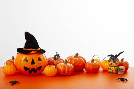 Happy Halloween pumpkin with festive decorations floor orange on white wall background. Empty space for the text design