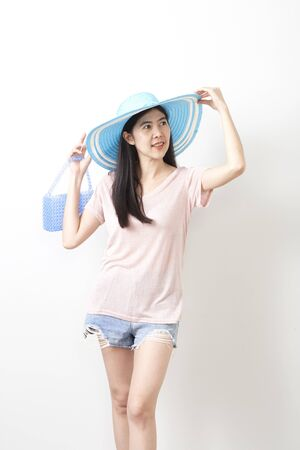 Asian young woman long haired in wearing denim shorts and straw hat holding the bag isolated on white wall background, 30-39 year old.