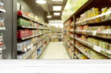 Empty white wood table blurry supermarket convenience store product shelf for background