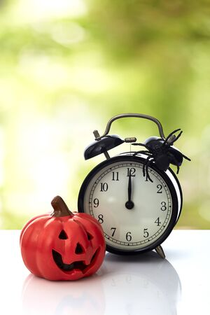 Vintage Clock with spider and pumpkin for Halloween celebration on white background, minimal copy space for text Stock Photo