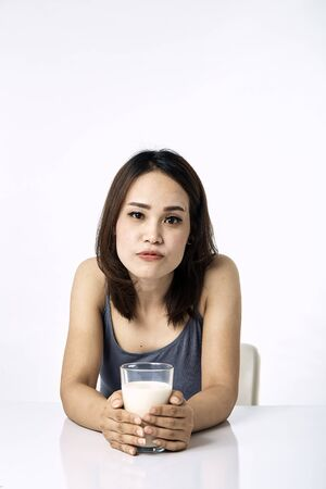 Portrait of beautiful young asian woman with a glass of on table white background, concept Healthy Lifestyle, cheerful girl in living room.