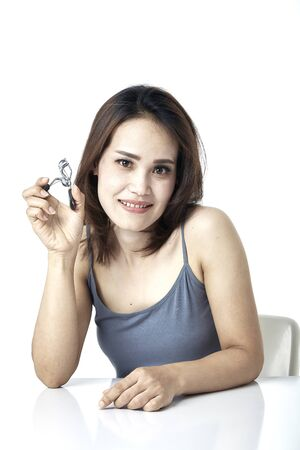 Beautiful young asian woman with eyelash curler on white background