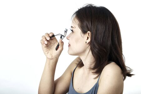 Beautiful young asian woman with eyelash curler on white background Stock Photo