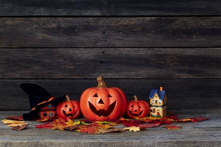 Happy Halloween pumpkin lantern. Trick or treat on a wooden table on a background of old wooden boards. Halloween background. Space for text.
