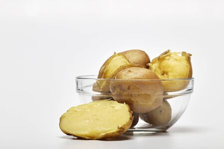 Boiled potatoes in a glass bowl on white background 写真素材