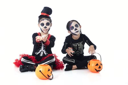 Asian children 5-8 years two children sitting on steps with trick or treat on white background