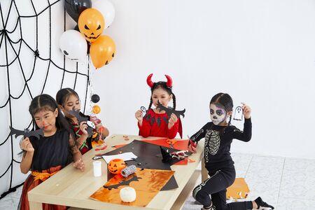 Feliz Halloween, grupo de disfraces de niñas de niños asiáticos La fiesta de Halloween tiene una diversión, truco o trato en casa