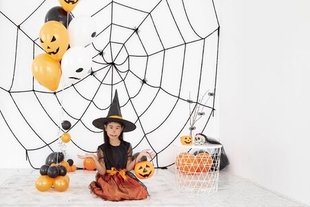 The concept of Halloween, funny face. Funny asian children girl in witch dress costume for Halloween decoration with pumpkins and holiday attributes. Children's party. Cute little witch dressed in hat with a pumpkin. 版權商用圖片