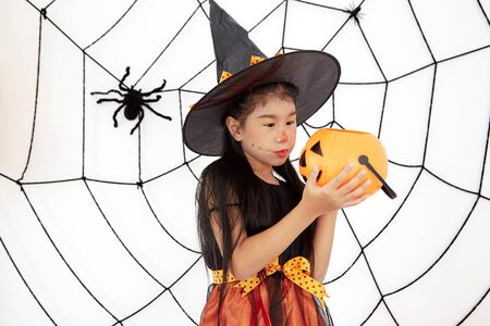 The concept of Halloween, funny face. Funny asian children girl in witch dress costume for Halloween decoration with pumpkins and holiday attributes. Childrens party. Cute little witch dressed in hat with a pumpkin.