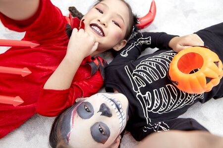 Two Asian child girls in halloween costumes with pumpkin, Funny kids in carnival costumes indoors Stock Photo