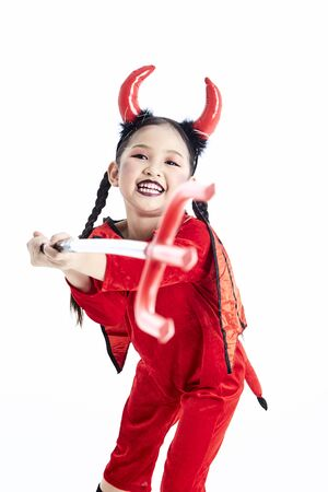 Little asian girl in a halloween fancy dress devil holding the trident and the blank board in a white studio