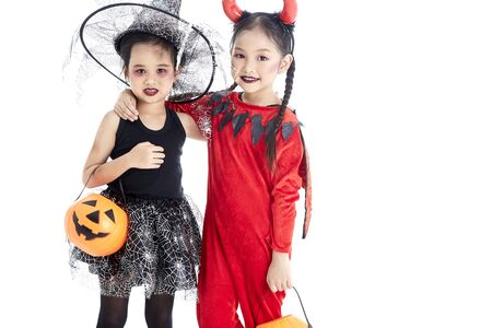 Two Little asian girl with face-paint in devil halloween and witch dress costume standing on white background