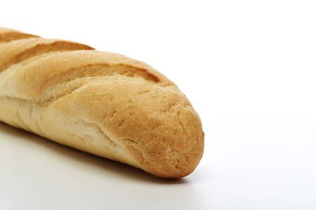 Cerrar pan francés de trigo rústico sobre un fondo blanco.
