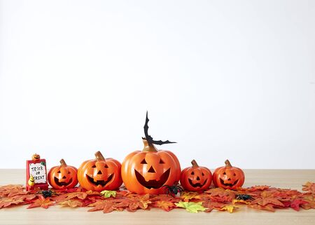 Halloween holiday decoration with pumpkin head jack lantern on table wood with white wall