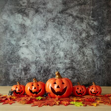 Halloween holiday decoration with pumpkin head jack lantern and autumn leaves on table wood with concrete wall Stok Fotoğraf