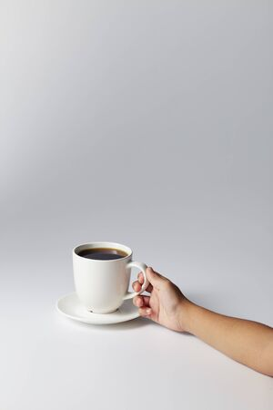 Hand holding a white cup of coffee on gray background