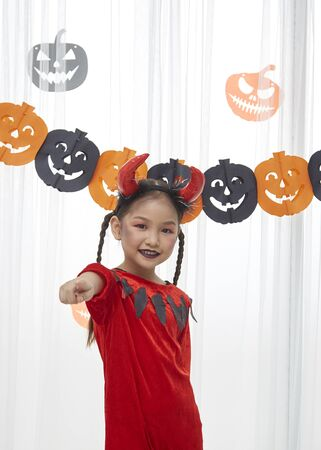 Portrait Asian cute little girl is wearing red devil costume at home, halloween holiday concept