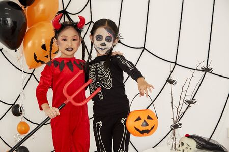 Two Asian child girls in halloween costumes with pumpkin, Funny kids in carnival costumes indoors 免版税图像