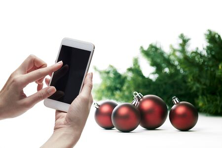 Mockup image of a female hand holding white mobile phone with blank black screen with christmas decorations background. copy space for text Stock Photo