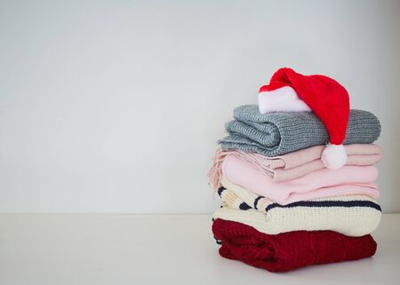 Pile of knitted winter clothes with Santa haton white table, sweaters, copy space for text Archivio Fotografico