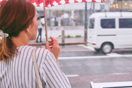 Asian mature woman smoking and standing at the street city when it rains, japan