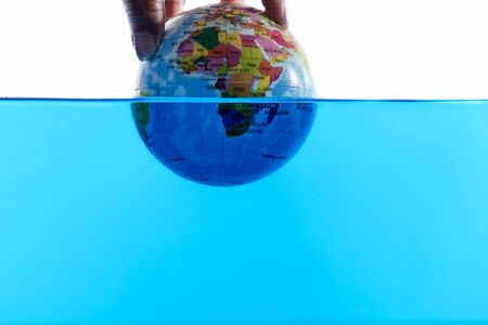 Hands and globes in the water, Global warming - drowning world - sea level rising