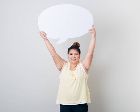 Asian Woman holding a blank field of white copy space shaped like a empty speech bubble studio shot isolated on light gray background 写真素材