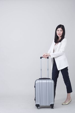 Beautiful young asian woman tourist smiling and pulling gray color luggage to travel on his vacation isolated on light gray studio banner background with copy space