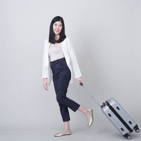 Beautiful young asian woman tourist smiling and pulling gray color luggage to travel on his vacation isolated on light gray studio banner background with copy space Banco de Imagens - 132104855