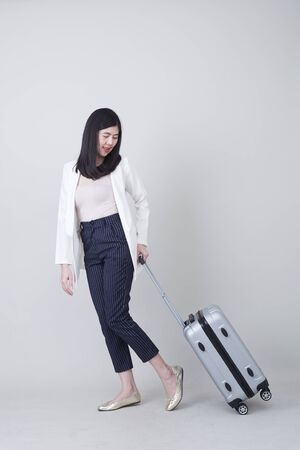 Beautiful young asian woman tourist smiling and pulling gray color luggage to travel on his vacation isolated on light gray studio banner background with copy space Banco de Imagens - 132104857