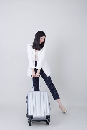 Beautiful young asian woman tourist smiling and pulling gray color luggage to travel on his vacation isolated on light gray studio banner background with copy space for text