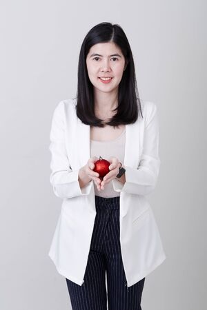 Portrait of a cheerful asian woman hand holding a christmas red ball  isolated on light gray studio banner background with copy space for text Stok Fotoğraf