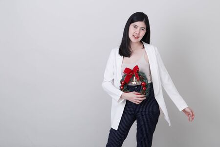 Portrait of a cheerful asian woman in christmas hand holding a wreath  isolated on light gray studio banner background with copy space