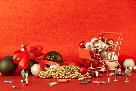 Miniature Shopping trolley with gift Christmas balls and with decoration on Defocused red lights background. Christmas and New Year sale, Online shopping Christmas