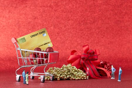 Miniature Shopping trolley with gift Christmas balls and  credit card on Defocused red lights background. Christmas and New Year sale, Online shopping Christmas, copy space for text Stock Photo