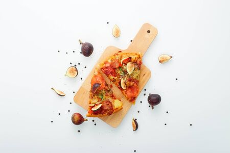 Flat lay. Slicing Pizza with figs a wood cutting board on table white, copy space for text Imagens