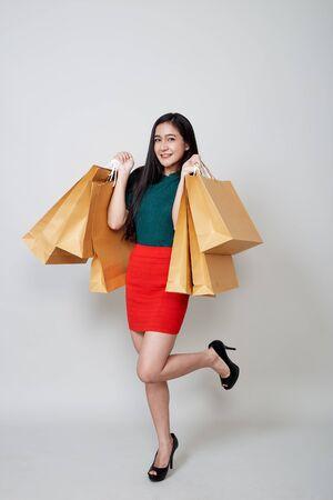 Belle femme asiatique joyeux Noël shopping tenant des sacs en papier pointe l'espace vide dans le studio sur fond gris clair