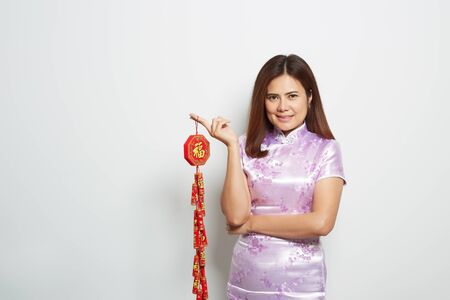 Woman asian in traditional chinese long dress holding Chinese firecrackers are a lucky amulet with Chinese characters that mean wealth. on white background, discount black friday