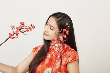 Young Asian woman in traditional chinese red dress with plum flowers Chinese new year's and Lunar new year decoration for Spring festival isolated on light gray banner background with copy space for
