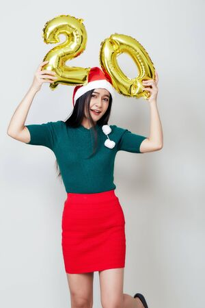 Portrait of young beautiful asian woman in fashion dress posing with gold 20 twenty number balloons isolated white background. Christmas and new year Credit and deposit installments concept. 版權商用圖片