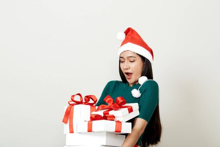 Beautiful Asian woman in in santa hat with many gifts studio shot isolated on bright gray background, copy space for text, Christmas Concept and new year