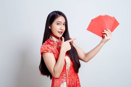 Asian women in chinese red dress feel happy with money in red envelopes on white background in Chinese new year
