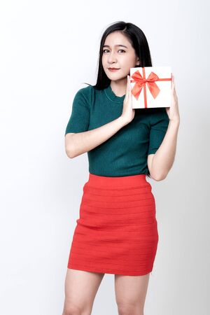 Happy young attractive asian woman holding gift box on grey background, new year, valentine day, birthday celebration concept, 스톡 콘텐츠