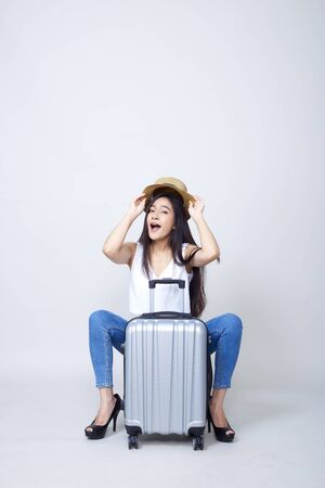 Travel concept. Studio portrait of pretty young asian woman holding passport and glass with suitcase and thinking about something. Isolated on white background, tourism, summer holidays and vacation