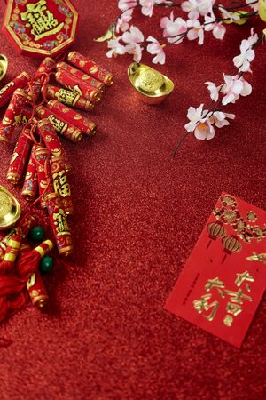 """Top view Decorate Chinese New Year Ornament or lunar new year on red background, Firecracker and Lucky Knot and Plum Blossom (with the character """"fu"""" meaning fortune)"""