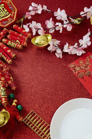 """Vue de dessus Décorez l'ornement du nouvel an chinois ou le nouvel an lunaire sur fond rouge, pétard et noeud porte-bonheur et fleur de prunier (avec le caractère """"fu"""" signifiant fortune)"""